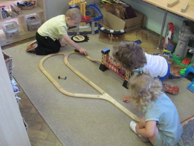 An image of three children playing on the floor with a simple wooden train set.